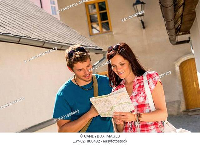 Happy couple looking at map in town