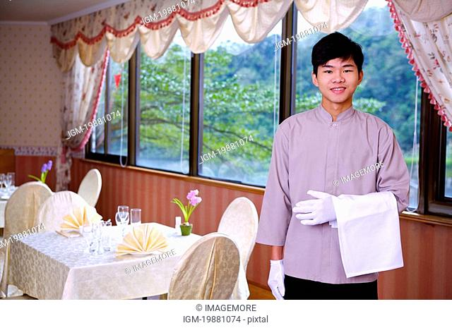 Young waiter holding a towel and smiling at the camera