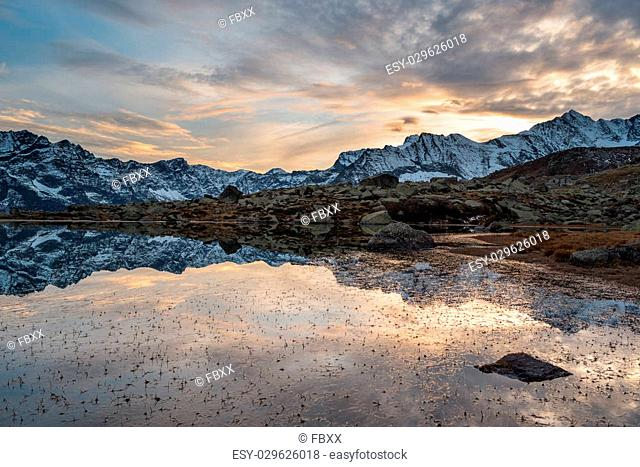 High altitude alpine lake in idyllic land once covered by glaciers. Reflection of snowcapped mountain range and scenic colorful sky at sunset