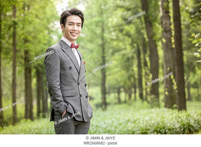 Young smiling groom posing outdoors
