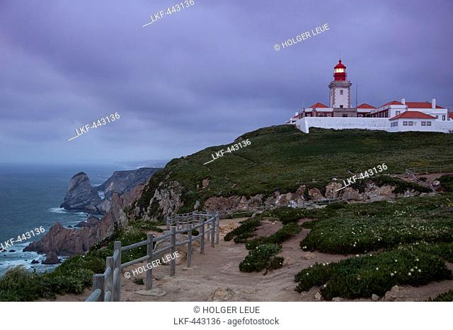 Cabo da Roca lighthouse overlooking the promontory towards the Atlantic Ocean at dusk (the most Western point of continental Europe), Near Cascais, Estremadura
