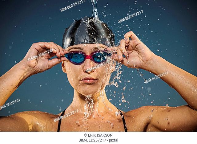 Water splashing on Caucasian woman adjusting swimming goggles