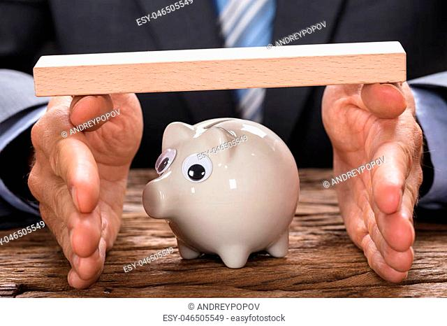 Midsection of businessman covering piggy bank with hands and wooden plank at table