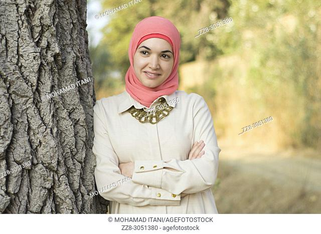 Happy Muslim woman wearing Hijab leaning against a tree looking away