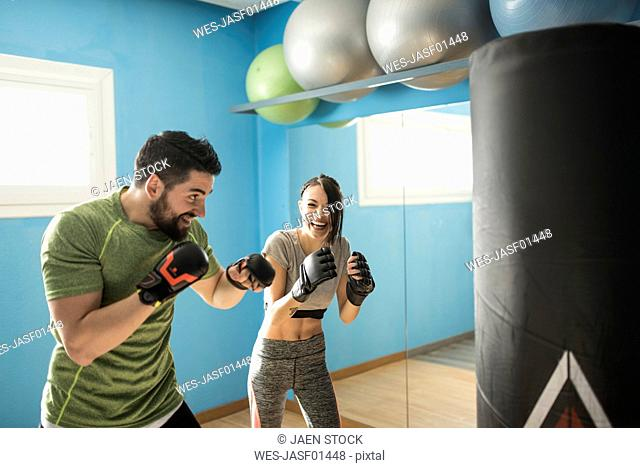 Coach exercising with woman at punching bag