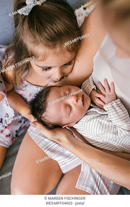 Mother holding her baby close with sister looking at him