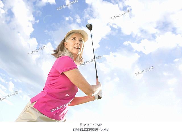 Caucasian woman swinging golf club