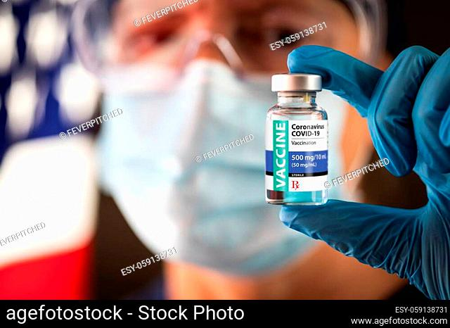 Female Medical Worker Holding Coronavirus Vaccine Vial Near American Flag Wearing Protective Face Mask and Goggles