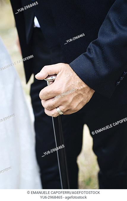 Senior groom with walking stick outdoors