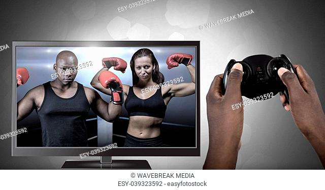 Hands holding gaming controller with boxing fighters on television