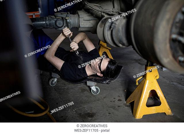 Female mechanic working at fire brigade workshop, lying on creeper