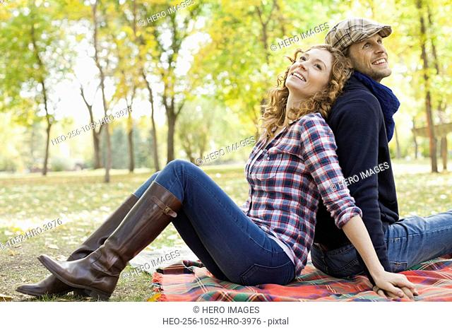 Happy mid adult couple sitting at park during autumn