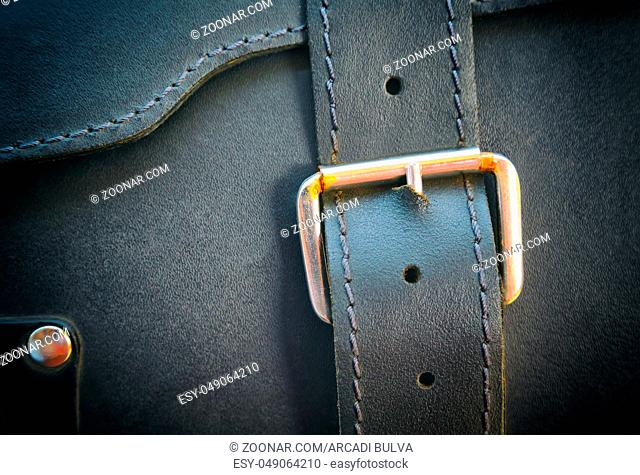 Texture of a black portfolio with a genuine leather buckle with embossed, close-up, texture for a designer, background, selective focus