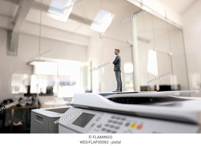Businessman figurine standing on copy machines in modern office