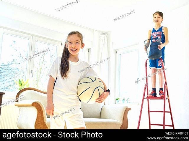 Portrait of girl and boy playing basketball in living room