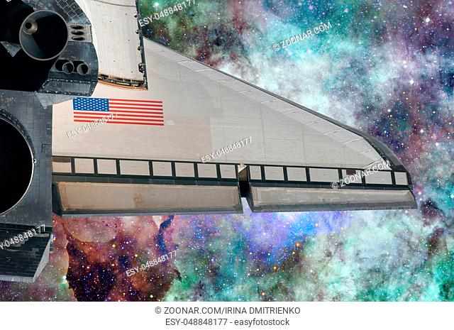 Space Shuttle over galaxy and space nebula. Elements of this image furnished by NASA