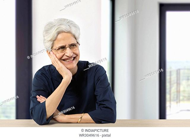 Happy senior woman with hand on chin looking away