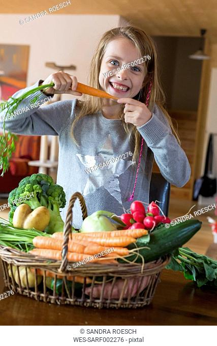 Portrait of girl with wickerbasket of fresh vegetables at home