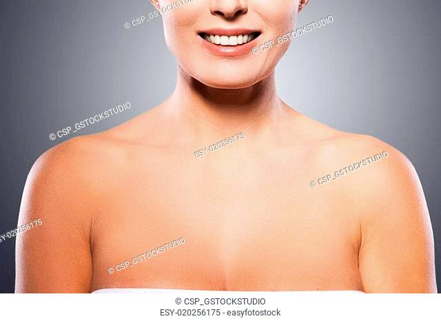 Natural beauty. Portrait of shirtless mature woman smiling while standing against grey background