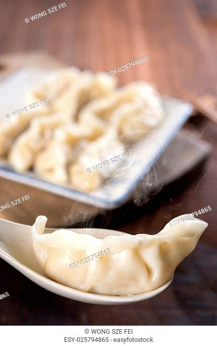 Close up fresh dumpling on spoon with hot steams. Delicious Chinese food on rustic old wooden background