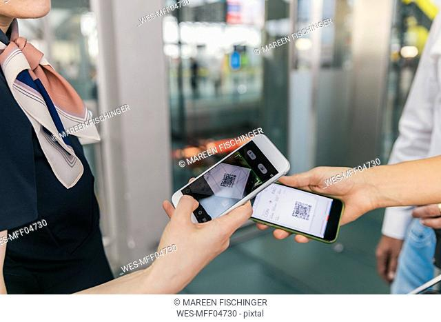 Airline employee scanning QR codes of passengers with smartphone at the airport