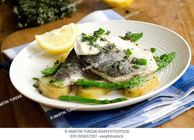 Grilled seabass with asparagus and new potatoes on a plate