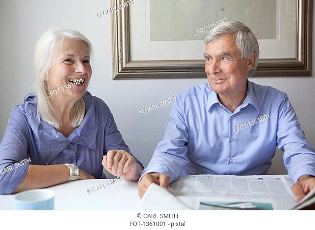 Happy senior couple with newspaper sitting at table in house
