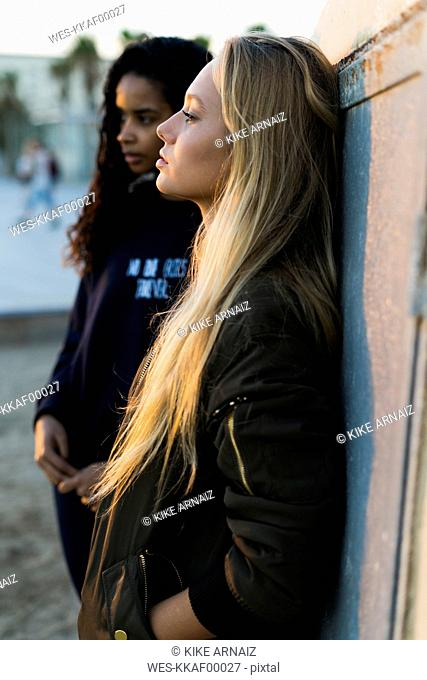 Two young women leaning against a wall at sunset