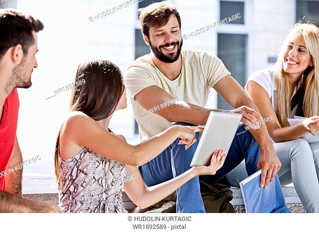 Group of university students using digital tablet together