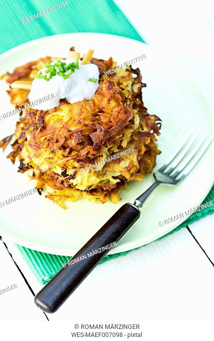 Plate of fried mashed potatoes with fork on wooden table, close up