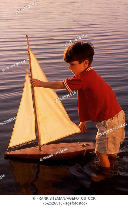 Boy, standing nearly knee deep in water, playing with toy sailboat in Upper Mystic Lake in Medford, MA, model released mr-5215