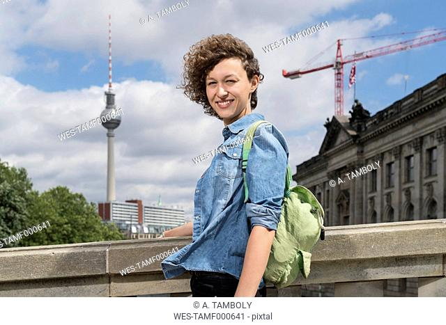 Germany, Berlin, portrait of smiling young woman standing in front of Bode Museum