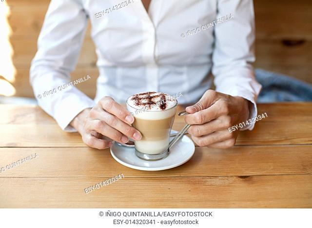 cappuccino coffee cup in hands of woman with white shirt on light brown wooden table cafe