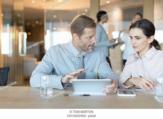 Businessman and businesswoman using digital tablet, talking in conference room meeting