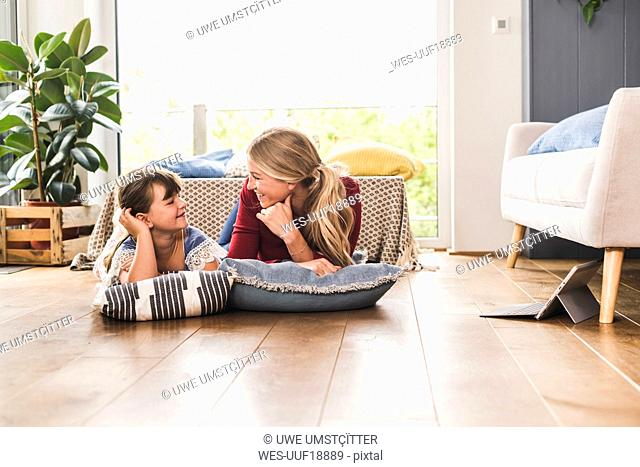 Mother and daughter lying on the floor at home looking at each other