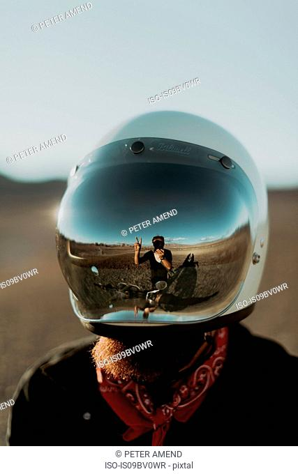 Motorcyclist's reflection on friend's helmet, Trona Pinnacles, California, US
