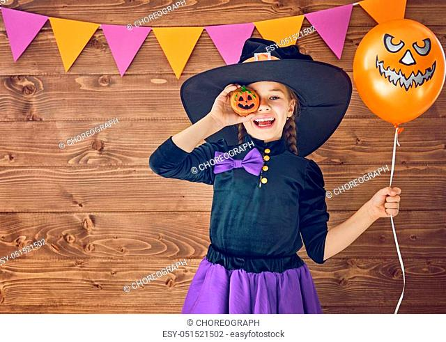 Happy Halloween! Cute little witch with a pumpkin air balloon