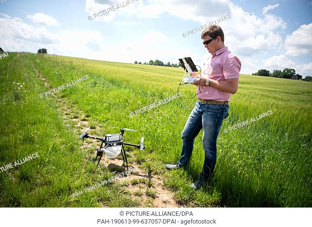 13 June 2019, Baden-Wuerttemberg, Freiberg am Neckar: Markus Schaible, farmer and contractor, fills his drone with capsules of ichneumon flies