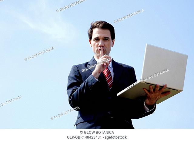 Businessman standing with finger on lips and holding a laptop