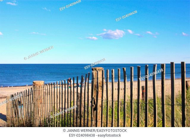 Blurred Background of New England beach lying in the afternoon sun, partly seen through a fence