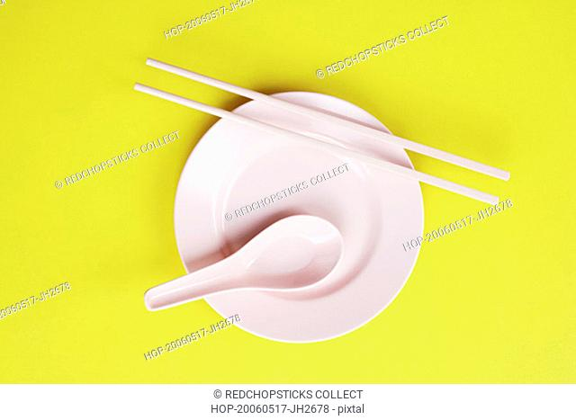 High angle view of a plate and a spoon with chopsticks