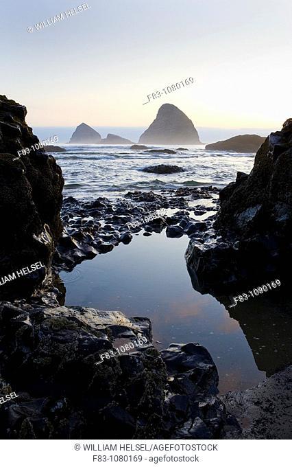 USA, Oregon, Tillamook County, Oceanside, sea stacks, rocky shoreline and tidepool, sunset, low tide, August