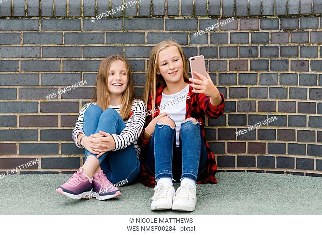 Portrait of two smiling girls sitting in front of brick wall taking selfie with smartphone