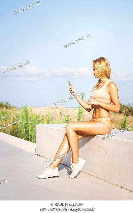 attractive female athlete looking at the phone before training, athletic sport girl consulting the app after running, technology fitness and healthy lifestyle...