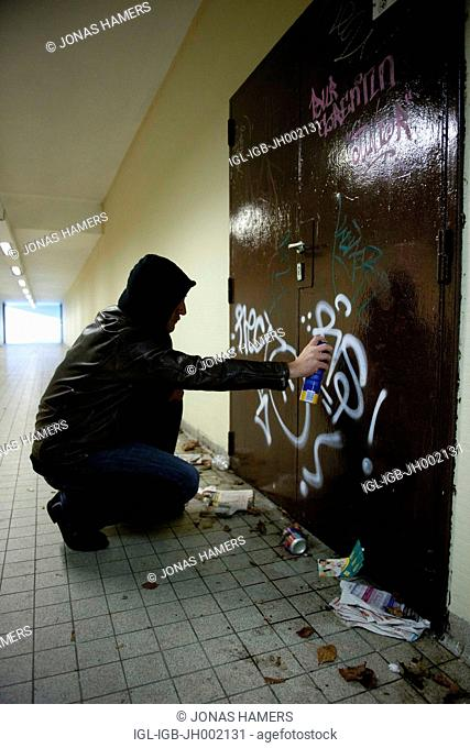 This picture shows tagger painting some graffitis on walls. Crime on the streets of a city may the creation of graffiti and vandalism of public property