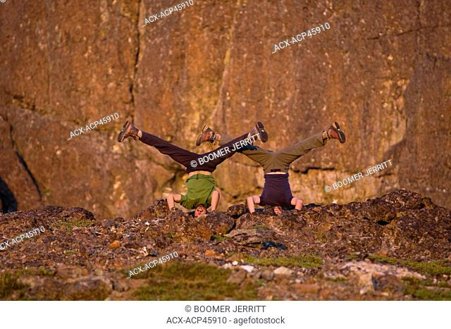 Two friends strike yoga poses at camp, while climbing the NorthWest ridge of Elkhorn Mountain. Strathcona Park, Central Vancouver Island, British Columbia