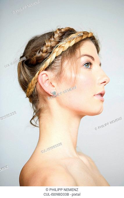 Beautiful young woman with bare shoulders and plaited hair, side view studio portrait