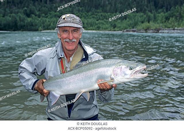 Flyfisherman Russ Fisher holding large summer-run steelhead prior to release, Dean river, British Columbia, Canada