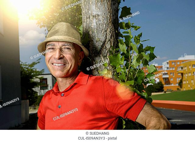 Portrait of smiling mature man wearing trilby hat leaning against park tree