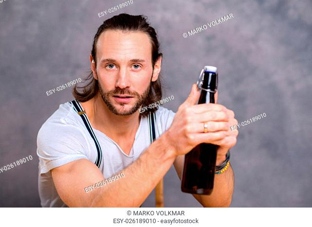 young man in front of gray background opening a beer bottle